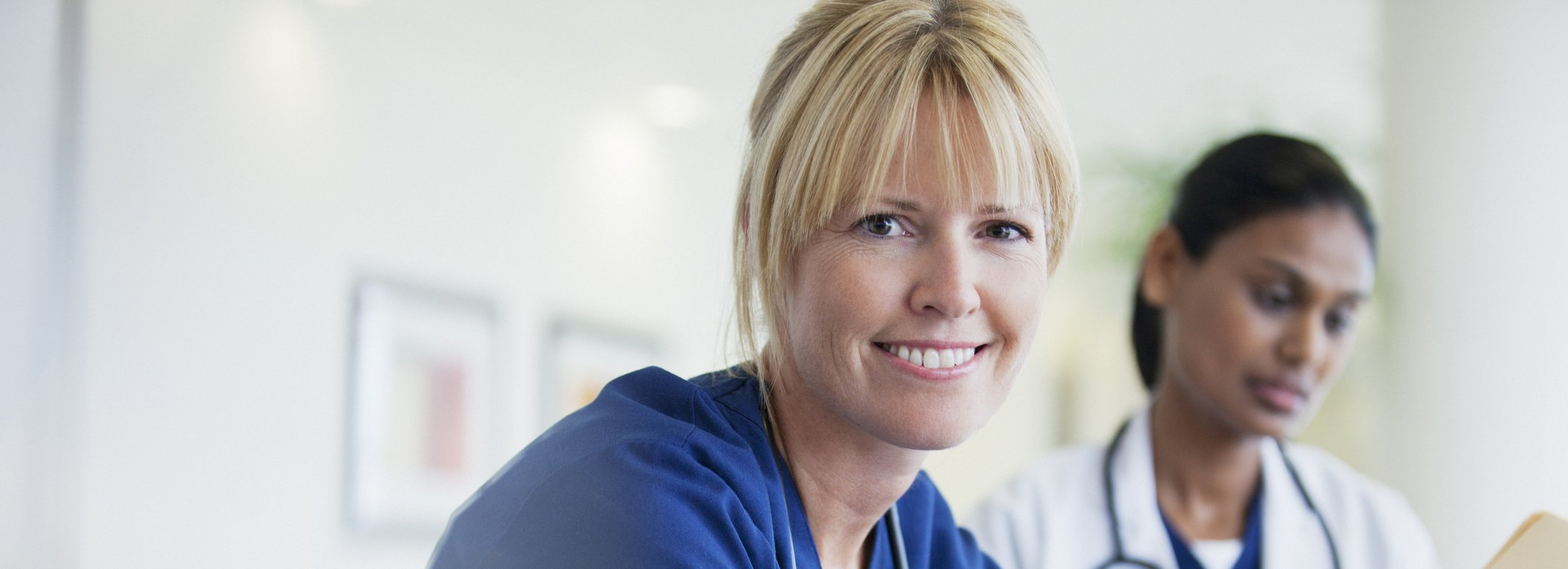 Portrait of smiling nurse sitting with doctor in hospital